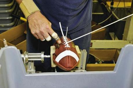 A football being laced up at Wilson Sporting Goods' factory in Ohio.
