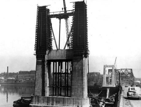 May 4, 1949: The lower half completed, forms went up for  concreting the upper pedestals of the Mystic River Bridge. To reach the top of the forms, the company pumped concrete 132 feet straight up. This photogr