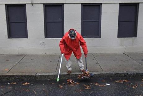 BOSTON MA.01/31/13: CIVIC TOUCH, Nhon Nguyen ( cq broken english ) cleans up the gutters ion the side of the apartment building where he works on Geneva Ave by Columbia Road, Boston .( David L Ryan/Globe Staff Photo ) SECTION: METRO TOPIC stand alone photo