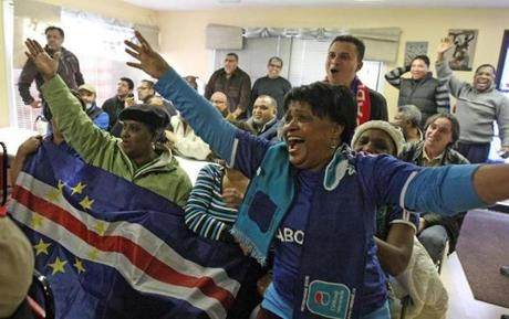 "Helena ""Ducha"" Antunes (foreground) and other fans cheer a shot by Cape Verde during Saturday's soccer match."