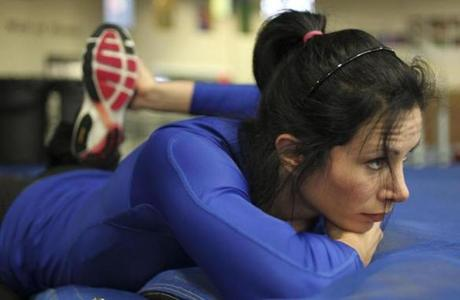 Olympian Jenn Suhr stretches before her training with her coach/husband Rick Suhr at Reggie Lewis Center. She'll be competing Saturday in the New Balance Grand Prix.