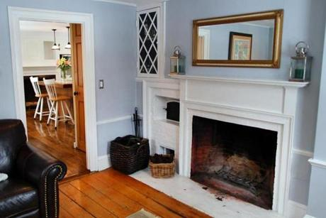 The living room has an original working brick fireplace, three large windows, and a small built-in cabinet.