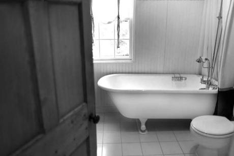 A full bath, located between the living room and kitchen, has a claw-foot tub.