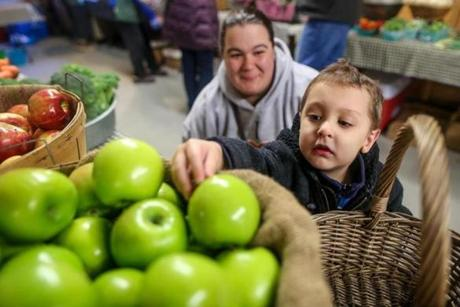 Kathy Trainor (left) of Taunton, watches her son John Trainor 4, choose an apple from the Oakdale Farms stand at the Easton Winter Farmers Market at Simpson Spring in Easton.