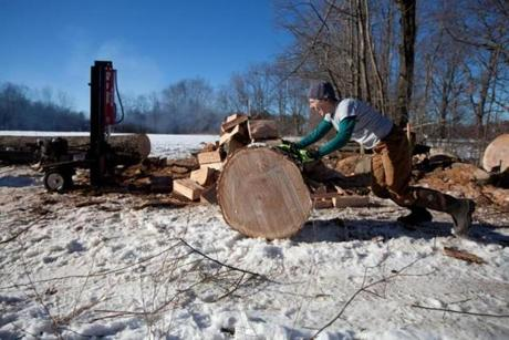 1/10/13 Orange, MA -- Anne Cavanaugh of Lowell, Mass. rolls a log to the splitter at the Farm School in Orange, Mass. January 10, 2013. Erik Jacobs for the Boston Globe
