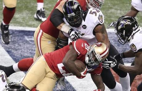 Frank Gore of the 49ers was tackled by Ray Lewis.