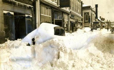 February 15, 1940: A parked car was completely covered in snow on Salem St. in Medford Square. (Notice that this print from our archive shows off the work of an airbrush artist in 1940. Every sign on this street was painted over, covering every business name.)