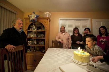 Johnston, RI - 1/27/2013 - Asher Nicholas O'Neill (cq) blows out the candles for Nick O'Neill (cq) who perished in the Station fire of 2003. At left is Nick's father, Dave Kane (cq). Dave Kane and his wife Joanne O'Neill invite a medium, Lisa Powers, to communicate with their son Nick O'Neill to celebrate what would be his 28th birthday at their home in Johnston, RI on Sunday, January 27, 2013. Nick died in the Station night club fire in 2003. (Yoon S. Byun/Globe Staff) Slug: 17nightclub Reporter: arsenault LOID: 5.1.450736470