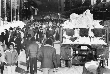 People walked by a snow truck on Boylston Street in the storm's aftermath.
