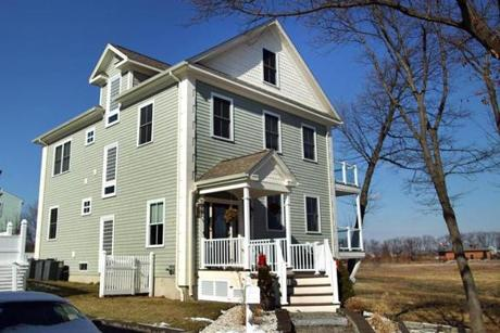 This towering Colonial in Adams Shore overlooks the Rock Island Cove Salt Marsh.