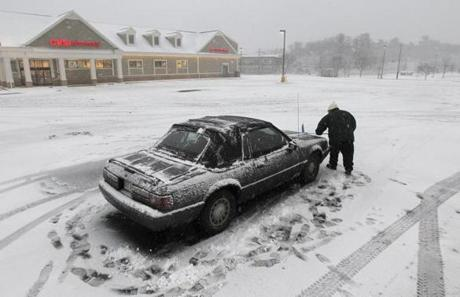 Millis, MA - 2/8/13 - Julie Verrochi (cq) cleans her car off (last one in parking lot) after leaving her job at Roache Bros. supermarket which closed early due to the storm. (Globe staff photo / Bill Greene) section: g, reporter: Kahn, topic: worm