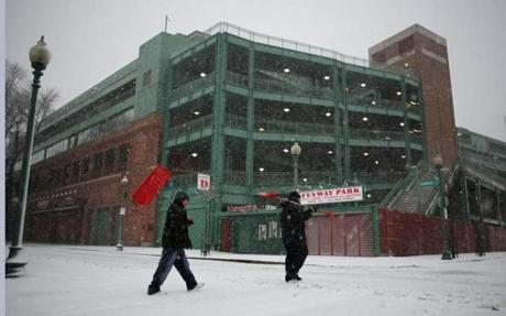 Boston-02/08/13-Alex Rodriguez(yes thats right)(cq) left, and Jesus Perez carry their shovels as they cross Yawkey Way past frozen Fenway Park on the way to their shoveling job for a nearby private contractor, as snow falls during the blizzard.Globe staff photo by John Tlumacki (metro)