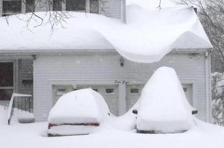 Snow buried cars and hung low off a roof in Wellesley.