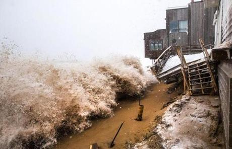 Waves crashed over sand barriers and destroyed the decks of shorefront houses on Plum Island.