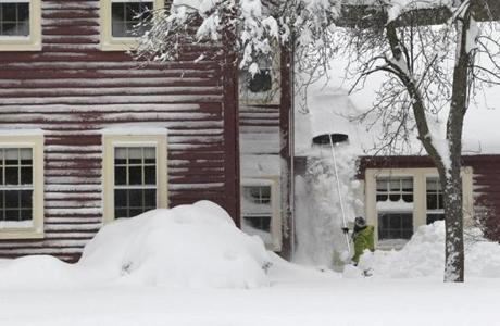 A Wellesley resident raked snow off her roof.