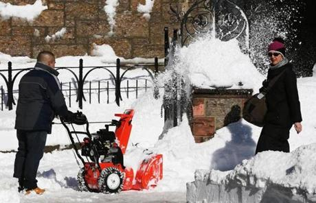 A woman walked past a man with a snowblower in Boston's Back Bay on Sunday.