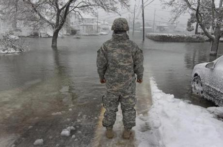 Private First Class Juan Jimens with the 1182d National Guard looked down flooded Turner Road in Scituate on Saturday. Storm surge forced some evacuations.