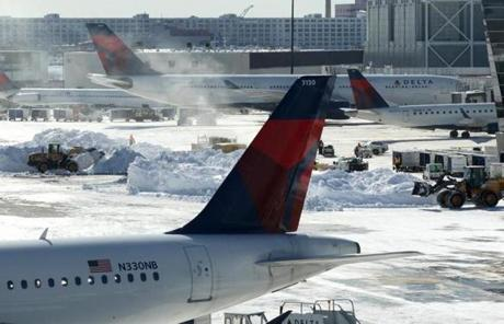 Snow removal continued Sunday at Logan Airport as flights resumed for the first full day since the storm.