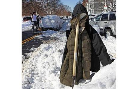 A coat hung on a shovel as South Boston residents dug out from the snowstorm Sunday.