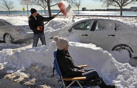 Jessica Mercaldi took a break as Sean Ledwidge shoveled out a car on Marine Road in South Boston.