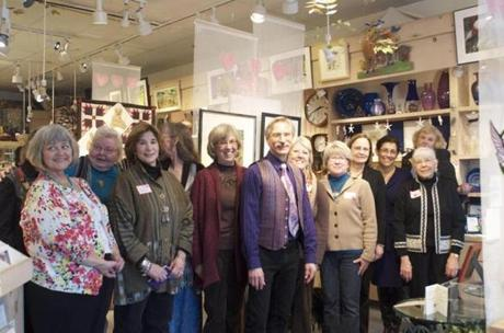 The 12 artists who submitted pieces to the exhibit who were present at the artist reception on Feb. 3 stood by the sides of gallery owner Glenn Johnson (center).