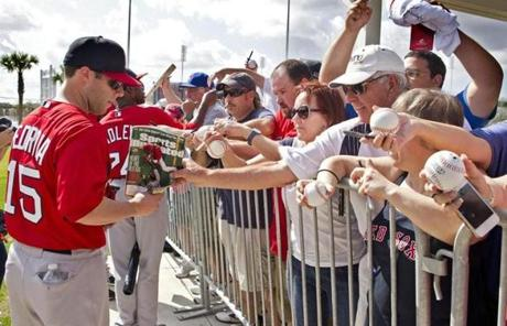 Dustin Pedroia signed autographs for fans after the first official workout for pitchers and catchers at Red Sox spring training Tuesday.
