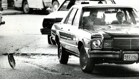 March 22, 1977: Two men in their clean shiny car hit a pothole under the Southeast Expressway after coming out of the Callahan Tunnel on Hanover Street. They lost their hubcap and were jounced around a bit in the car.