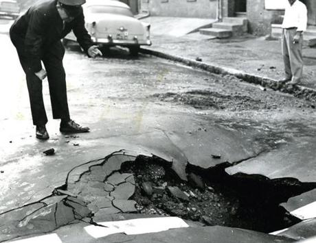 October 13 1961: A broken water main created a large sinkhole at East Brookline and Harrison Avenue in the South End as Boston police officer Joseph Gorman got in the picture.