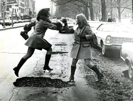 February 9, 1970: Glee Corsetti (left) and Peggy Mahoney, both of Wilmington, helped each other negotiate a pothole on Boylston Street in Boston. They had their pick of potholes to jump over.
