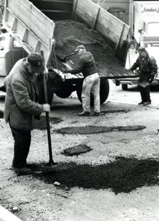 April 10, 1963:  Ed Walsh tamped down asphalt as Salvatore Tortora and Nick Migliozzi brought more from the truck. The 1963 road repair campaign would require some 8,000 tons of asphalt for pothole repairs in the city.