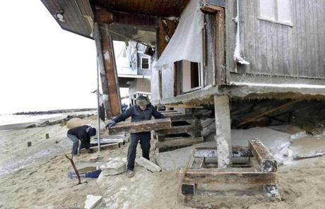 Tom Nee carried wood to shore up the foundation of his damaged home on Plum Island.