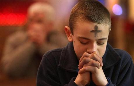 Myles Toole, 12, from Kingston, prayed after receiving ashes at St. Anthony Shrine.