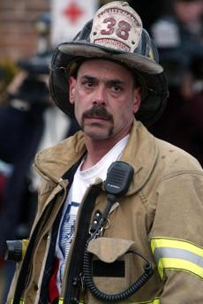 An unidentified firefighter wearing a Coventry, R.I., jacket paused before entering a makeshift Red Cross station to rest.