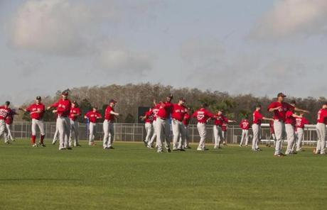Red Sox pitchers stretched on a practice field during the second day of spring training at JetBlue Park in Fort Myers, Fla.