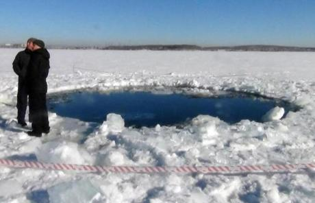 A 20-foot-wide hole was left in the ice of a frozen lake from a suspected meteor strike outside the town of Chebakul, Russia.