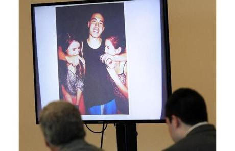 Nathaniel Fujita, lower right, sat in the courtroom as a party photo of him and two friends was shown on a screen.
