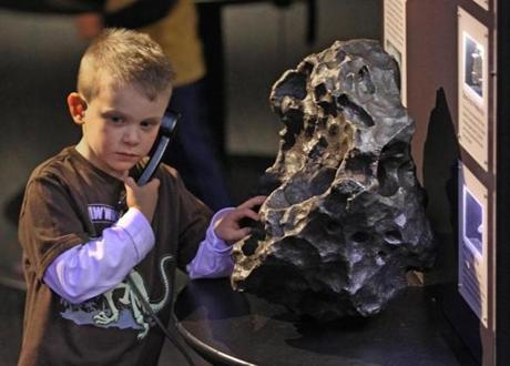 BOSTON MA. 02/20/13: SCHOOL VACATION WEEK, children enjoy the Museum of Science this week off from school. Young scientist Chase O'Donnell ( cq) from Milford listens about a 300 lbs meteorite part of a 300,000 ton meteorite that crashed into an Arizona desert 50,000 yrs ago at the Science in the Park exhibit. ( David L Ryan/Globe Staff Photo ) SECTION: METRO TOPIC stand alone photo