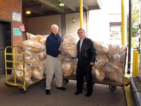 Temple Emanuel Brotherhood members Dennis Buchenholz (right) and David Greenfield of Newton load bulk mailing bags containing 1,100 Jewish National Fund collection boxes onto a mail truck for delivery to congregation families at the West Newton Post Office in October 2012. The project is part of the brotherhood's Roots in Israel initiative.