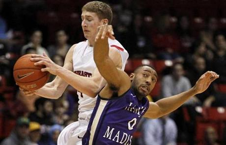 Northeastern guard David Walker was fouled by James Madison University guard A.J. Davis as Walker tried to catch a pass at half court.