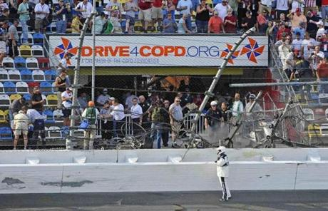 Rescue workers stood next to a hole in the catch fence following the crash.