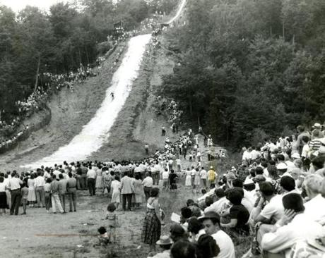 July 25, 1950 / The crowd in Laconia, N.H. lined the slopes in shirtsleeves and summer garb as one of the contestants in the annual summer ski jump landed down the hill. Some 100 tons of crushed ice was spread over the inrun, takeoff and landing hill for this popular summer event which featured top US ski jumpers.