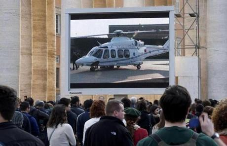 People in Saint Peter's Square watched the screen of the helicopter waiting to carry Pope Benedict XVI.