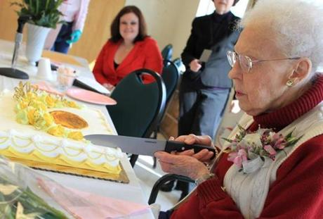 Reed cut her cake after receiving a Boston Post Cane plaque. The Boston Post Cane tradition is still carried on by many towns in New England.