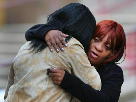 Two women hugged after leaving a hearing in Roxbury District Court for two men suspected of shooting to death a man on the platform of the Dudley Square bus platform.