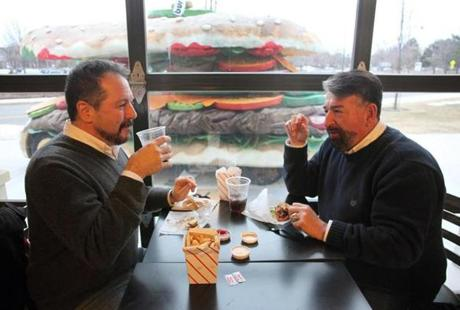 Glenn Pacheco, left, and Bill Philbrook, both of Somerville, eat at a table with a burger car parked outside the window.