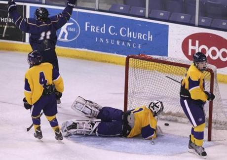 Malden Catholic's Tyler Sifferlen (background) celebrates his goal past Springfield Cathedral goaltender John Liquori.