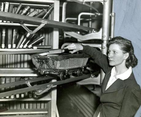 May 22, 1938:  Mary J. Coyle loaded a book cart deep in the stacks to carry the book freight to the delivery desk using the library's interior electric railway system. Tiny cars with a capacity of about a dozen books each ran constantly from the depths of the stacks to the circulation desk in response to slips from patrons which were electrically dispatched from the desk.
