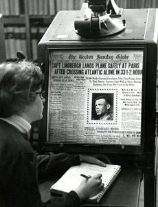 March 28, 1965: Kathleen Mitchell, a student at Suffolk University, read details of Charles Lindbergh's famous solo flight to Paris in the Sunday Globe of May 22, 1927 from the microfilm reader in the the newspaper room.