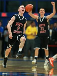 North Quincy guard Daniel Gould (5) leaped and yelled in celebration as the final horn sounded in his team's victory as teammate Efthim Butka (31) joined in. Newton North and North Quincy met in a Division One South boy's basketball tournament game held at the Clark Center on the campus of UMass Boston.