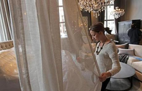 Restoration Hardware employee Danielle Bolas sprayed linen as workers set up the new store,